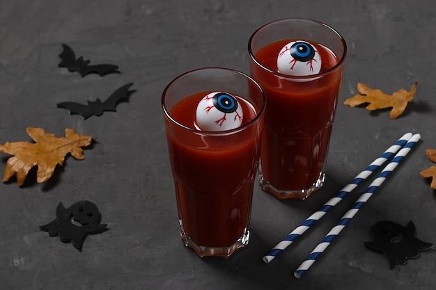 Olhos em vidro com coquetel de tomate na mesa cinza escura para o feriado de outono, halloween.
