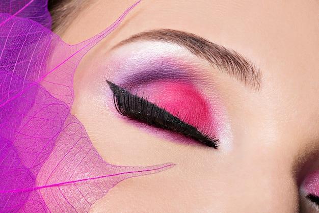 Olhos femininos com bela maquiagem rosa brilhante fashion