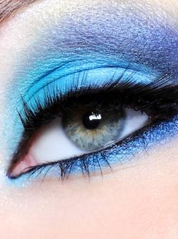 Olhos femininos com maquiagem azul brilhante - foto macro