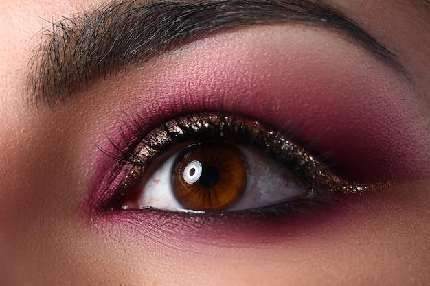 Olhos femininos com sobrancelhas e maquiagem em tons de rosa