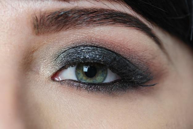 Olhos femininos e sobrancelha com close-up de maquiagem