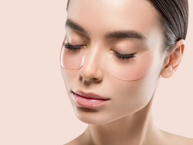 Olhos mascaram cosméticos de rosto de mulher asiática. cor de fundo. cor de rosa