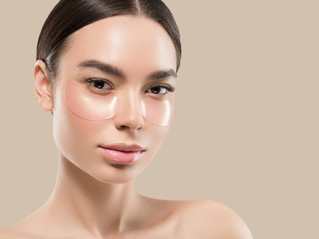 Olhos mascaram cosméticos de rosto de mulher asiática. cor de fundo. marrom.
