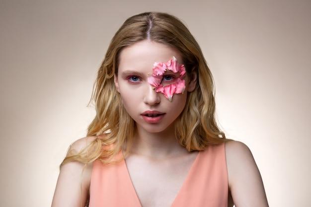 Olhos rosa. modelo com cabelo loiro ondulado e viseira rosa com pétalas de flores ao redor dos olhos