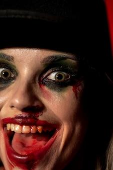 Olhos verdes de uma maquiagem de palhaço de mulher louca