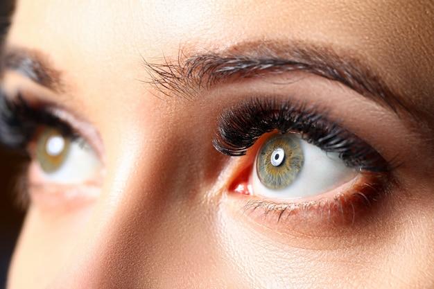 Olhos verdes femininos incríveis com close-up de extensões de cílios