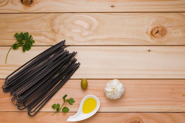 Oliva; alho; massa de arroz preto cru salsa e cru na mesa de madeira