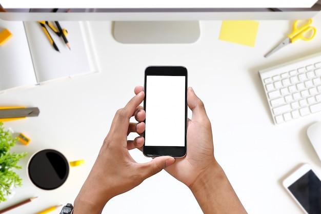 Omã mãos segurando um telefone inteligente com tela de espaço em branco cópia na mesa do escritório.