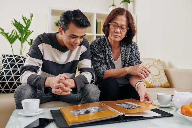 Omã mostrando fotos antigas para o filho