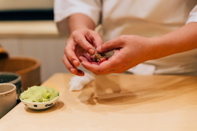 Omakase chef japonês fazendo chutoro sushi (atum rabilho médio gordo).
