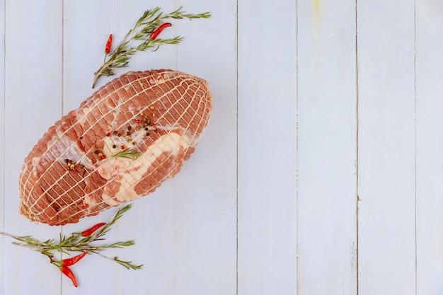Ombro de porco assado com especiarias na mesa de madeira branca. vista do topo