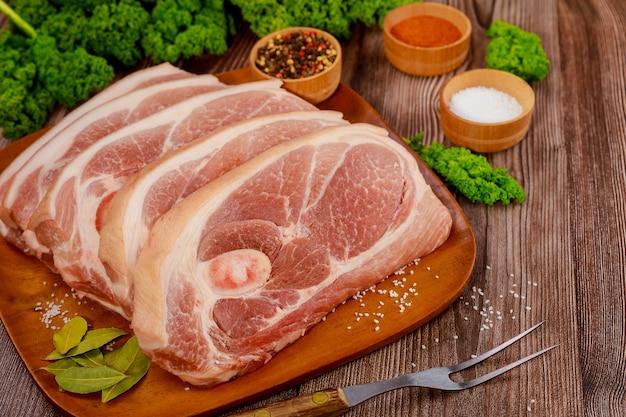 Ombro de porco cru fatiado com especiarias e um garfo na placa de madeira.
