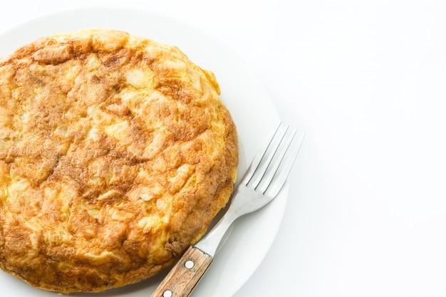 Omeleta espanhola tradicional e garfo isolado no branco
