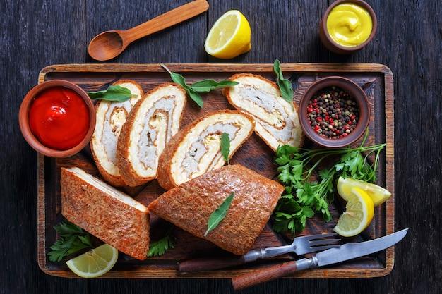 Omelete assado com carne picada de frango em uma bandeja de madeira rústica servida com limão, molho de tomate e mostarda em uma mesa de madeira escura, vista horizontal de cima, camada plana
