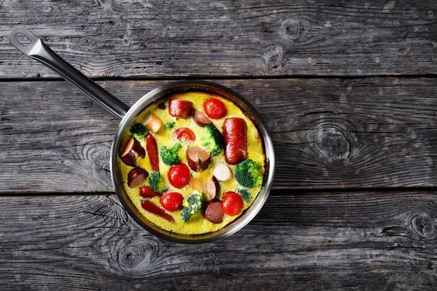 Omelete assado ou fritada com salsichas, brócolis, tomate cereja, queijo derretido em uma frigideira sobre uma mesa rústica de madeira