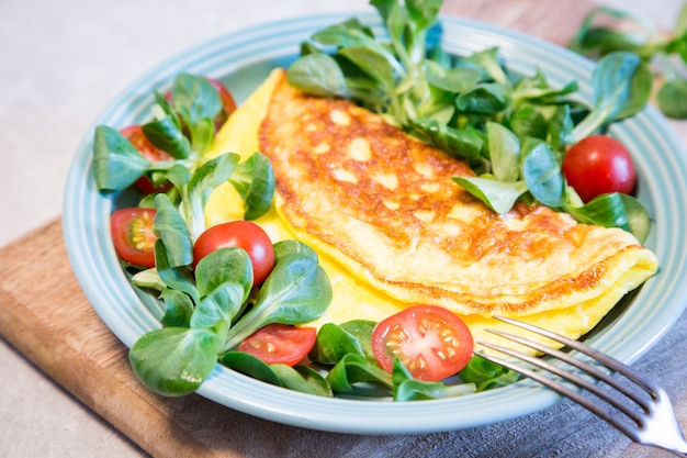 Omelete caseiro com salada no prato. conceito de comida saudável