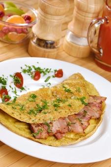 Omelete com bacon servido no prato branco
