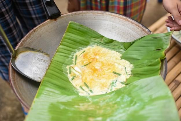 Omelete com cebola verde em uma folha de bananeira na panela café da manhã omelete de ovo frito sem óleo