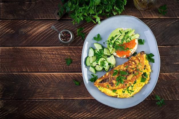 Omelete com cogumelo da floresta, macarrão fusilli e sanduíche com cavier vermelho, abacate no prato. frittata - omelete italiana. vista superior, sobrecarga, espaço de cópia