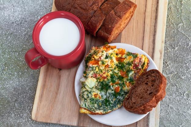 Omelete com ervas, pão e caneca de leite na placa de madeira no café da manhã