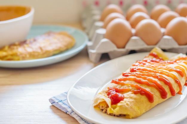 Omelete com ketchup no topo em um prato branco com uma bandeja de ovo borrão como pano de fundo