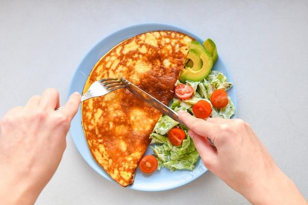 Omelete com legumes em um prato. prato azul. vista de cima. omelete com legumes em um prato servido no café da manhã. vista de cima