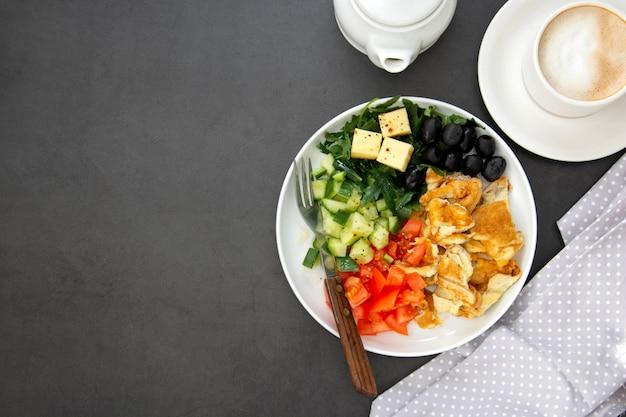 Omelete com legumes frescos: rúcula, tomate, pepino, azeitonas, queijo. mesa escura com espaço de cópia. vista do topo.