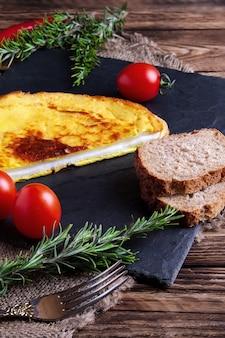 Omelete com pão integral e tomate fresco