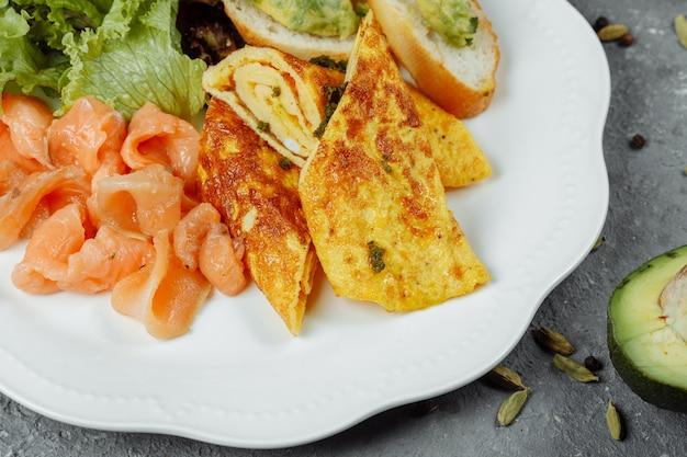 Omelete com peixe vermelho e vegetais, bela porção.