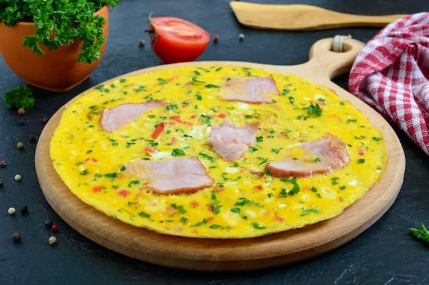 Omelete com presunto, queijo, verduras em uma placa de madeira sobre um fundo preto. fritata - um delicioso e saudável café da manhã.
