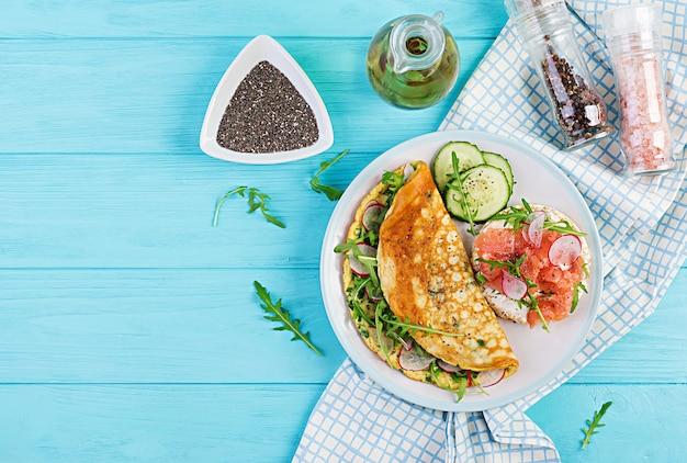 Omelete com rabanete, rúcula verde e sanduíche com salmão no prato branco
