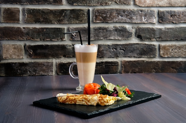 Omelete com salmão no prato de ardósia e xícara de café com leite