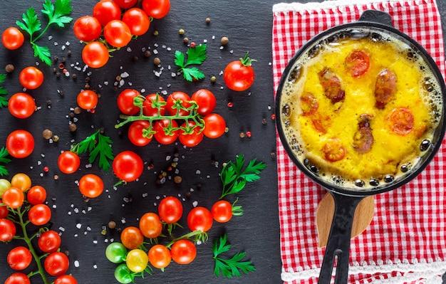 Omelete com salsichas e ovos de galinha em uma panela redonda de ferro fundido