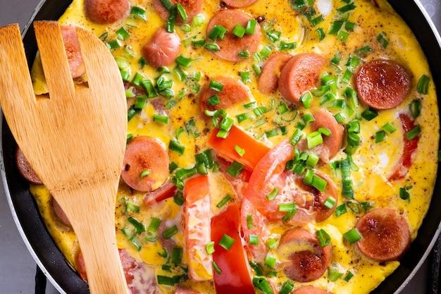 Omelete com tomate, cebola e linguiça na frigideira com espátula de madeira