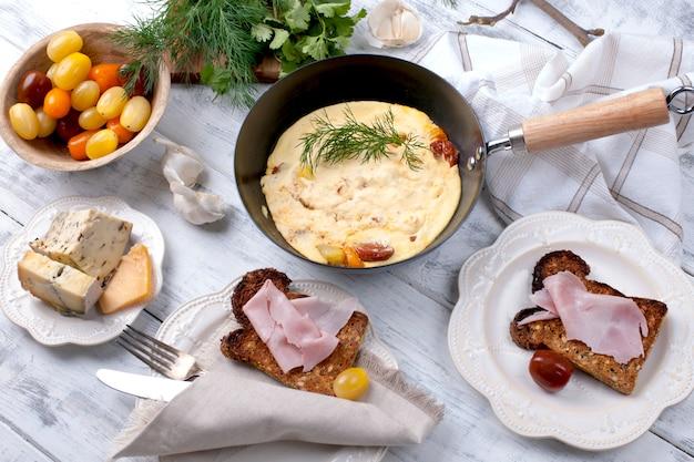 Omelete com tomate em uma frigideira no café da manhã, queijo e verduras em um fundo branco de madeira