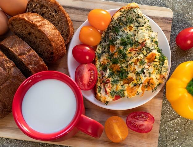 Omelete com tomate, ervas, pão e pimentão na placa de madeira no café da manhã