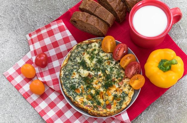 Omelete com tomate, ervas, pimentão e caneca de leite em guardanapo de linho no café da manhã