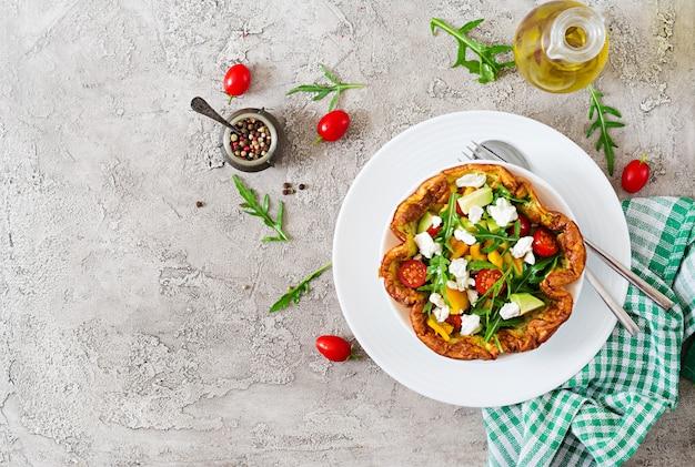 Omelete com tomate fresco, abacate e queijo mussarela. salada de omelete