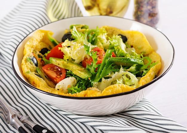 Omelete com tomate fresco, azeitona preta, abacate e queijo mussarela.