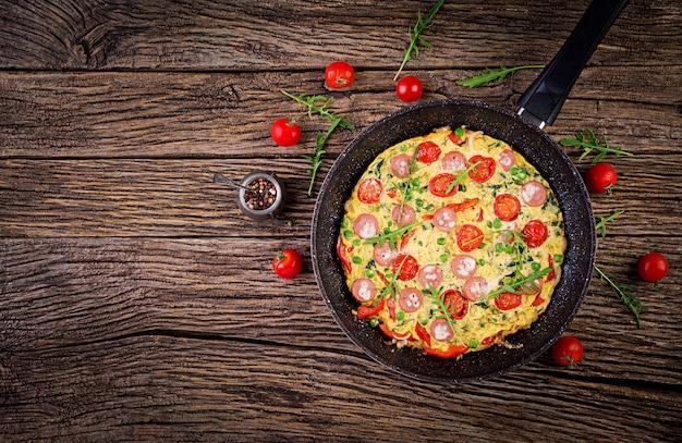 Omelete com tomate, linguiça e ervilhas em estilo rústico