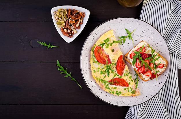 Omelete com tomate, presunto, cebola verde e sanduíche com morango na mesa escura