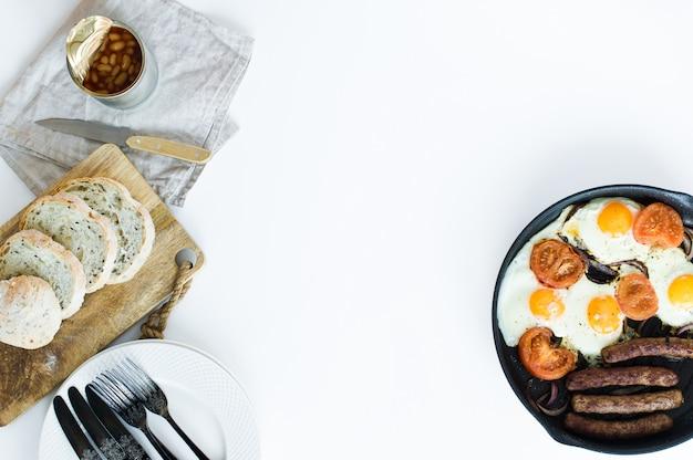 Omelete com tomates em uma panela sobre um fundo branco.