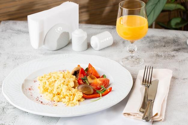 Omelete com vagetable, espinafre, tomate cereja e suco de laranja fresco isolado na mesa de mármore branca. comida caseira. saboroso café da manhã. foco seletivo. foto hotizontal.