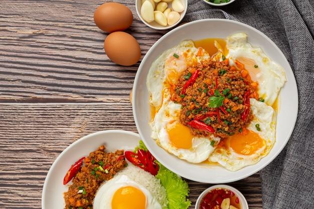 Omelete crocante coberto com carne de porco picada e molho de vegetais mistos
