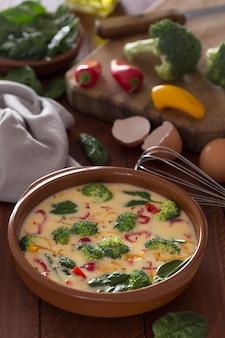 Omelete cru preparado e ingredientes em cima da mesa