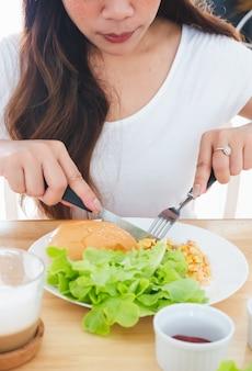 Omelete de café da manhã, pão, hambúrguer e legumes em um prato branco, usando uma faca e um garfo