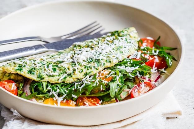 Omelete de espinafre verde com queijo, rúcula e tomate em chapa branca.