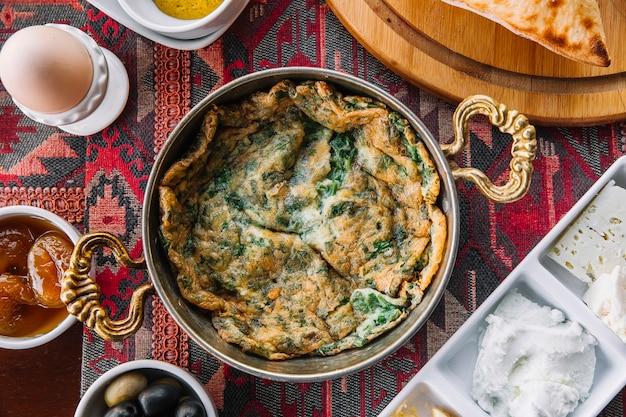 Omelete de kyukyu de vista superior com ervas em uma panela