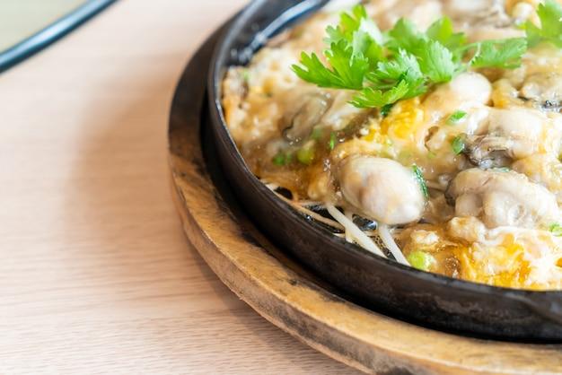 Omelete de ostra com broto de feijão na frigideira quente