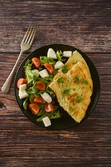 Omelete de ovo com tomate cereja, mussarela e salada verde. mesa de madeira com espaço de cópia.